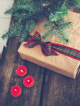 Regalo de navidad con linda cinta y velas.