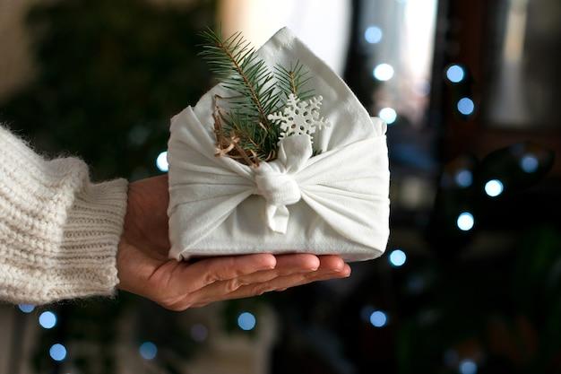 Regalo de navidad en las manos. embalaje en materiales ecológicos