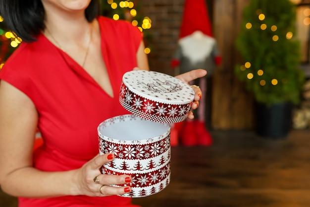 Regalo de navidad en manos de mujer, fondo de año nuevo