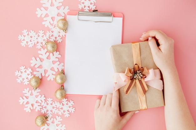 Regalo de navidad en manos de las mujeres y cuaderno sobre un fondo rosa