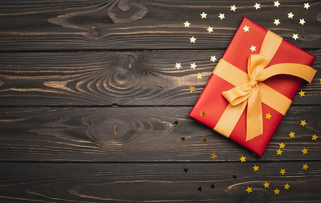 Regalo de navidad sobre fondo de madera y estrellas doradas