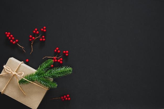 Regalo de navidad sobre fondo negro con ramas de pino, bayas y cuerda