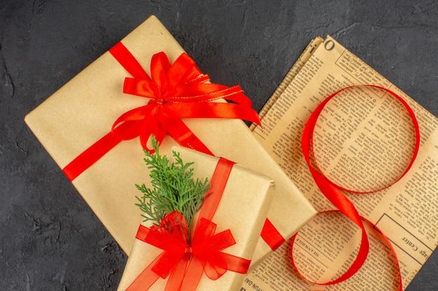 Regalo de navidad de la vista superior cercana en cinta de abeto de rama de papel marrón en periódico sobre fondo oscuro