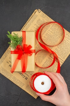 Regalo de navidad de vista superior en cinta de abeto de rama de papel marrón en mano femenina sobre superficie oscura