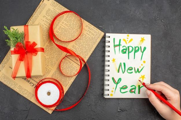 Regalo de navidad de vista superior en cinta de abeto de rama de papel marrón en periódico feliz año nuevo escrito en lápiz de bloc de notas en mano femenina sobre superficie oscura