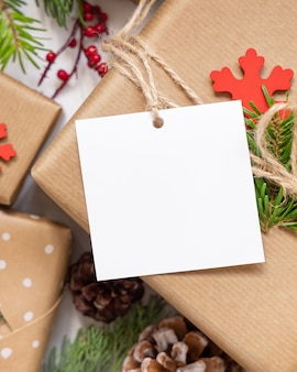 Regalo de navidad con vista superior de etiqueta de regalo cuadrada en blanco, maqueta