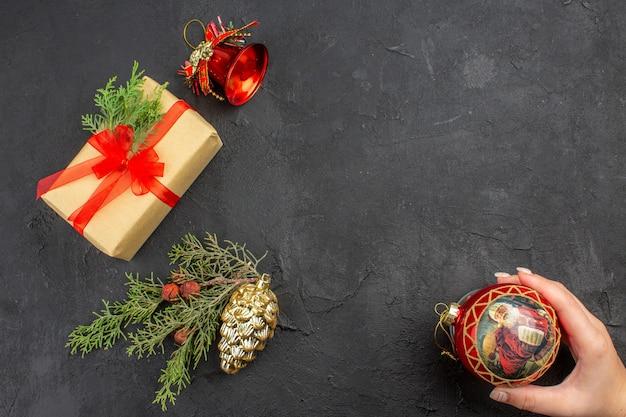 Regalo de navidad de vista superior en papel marrón atado con cinta roja adornos de árbol de navidad bola de navidad en mano femenina sobre superficie oscura