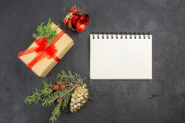 Regalo de navidad de vista superior en papel marrón atado con cuaderno de adornos de árbol de navidad de cinta roja sobre superficie oscura