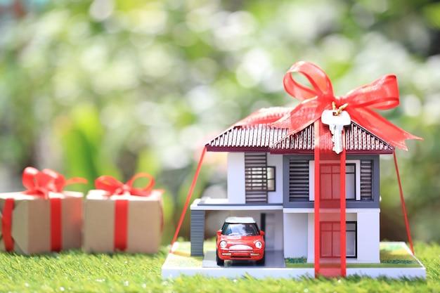 Regalo nuevo hogar y bienes raíces, casa modelo con cinta roja y el automóvil en verde natural