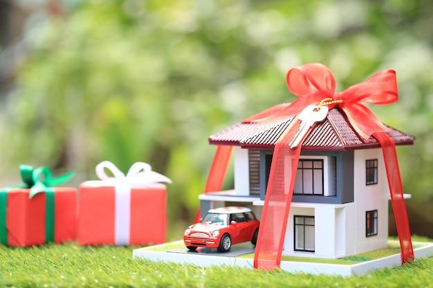 Regalo nuevo hogar y concepto inmobiliario, casa modelo con cinta roja y el automóvil sobre fondo verde natural