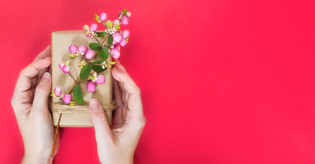 Regalo en papel artesanal con rama con bayas rosadas de snowberry rosa en manos de mujer con espacio de copia.