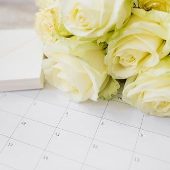 Regalo y ramo de rosas amarillas en calendario.