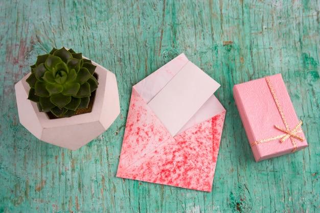 Regalo rosa, maceta suculenta y sobre con papel blanco en blanco simulado fondo de madera en mal estado