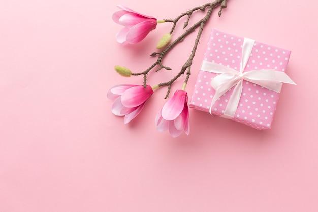 Regalo rosa con magnolia y copia espacio