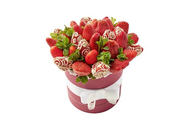 Regalo sabroso y saludable en forma de caja llena de fresas maduras decoradas con chocolate blanco