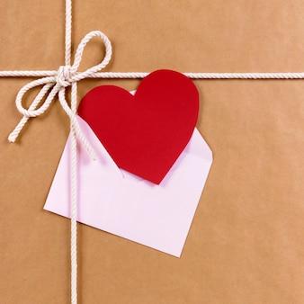 Regalo de san valentín con tarjeta de corazón rojo o etiqueta de regalo, paquete de papel marrón