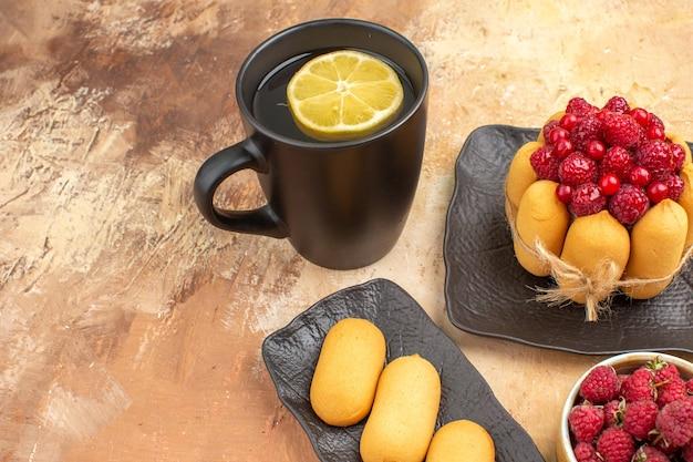 Un regalo de tarta y té en una taza negra con limón y galletas en la mesa de colores mezclados vista cercana