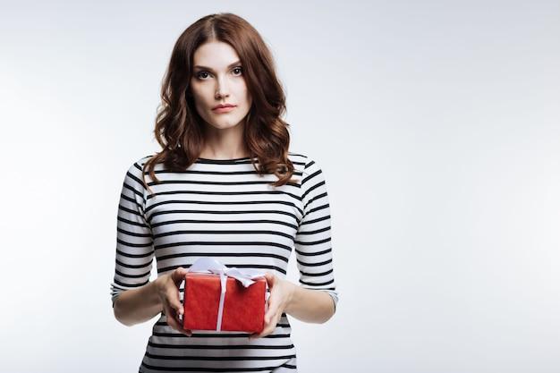 Regalo para usted. bonita mujer joven de pelo castaño con un jersey de rayas sosteniendo una caja de regalo bellamente envuelta mientras posa sobre fondo gris