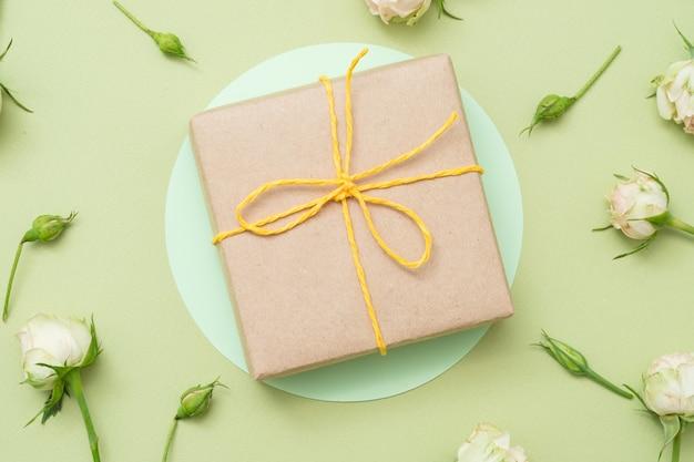 Regalo de vacaciones. caja de regalo de papel artesanal. decoración rosa mínima en mesa verde.