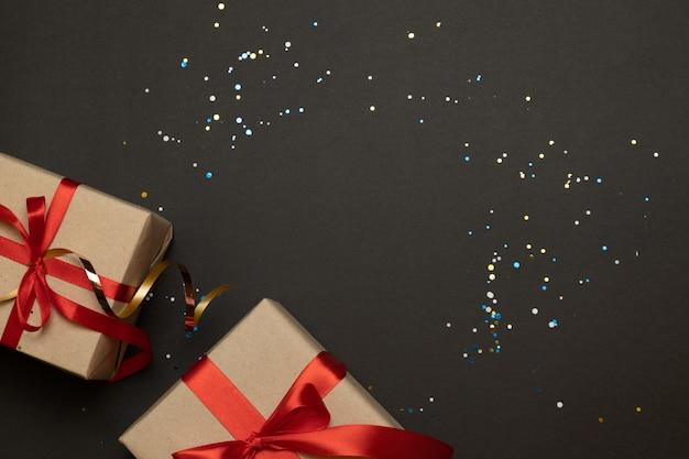 Regalos artesanales de navidad con cintas rojas y confeti dorado sobre un fondo oscuro en contraste