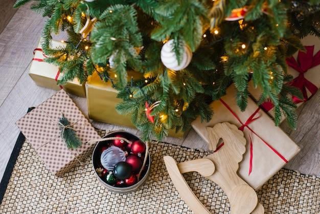 Regalos y un caballo de madera se encuentran debajo del árbol de navidad