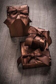 Regalos en caja en papel brillante con cintas marrones versión vertical
