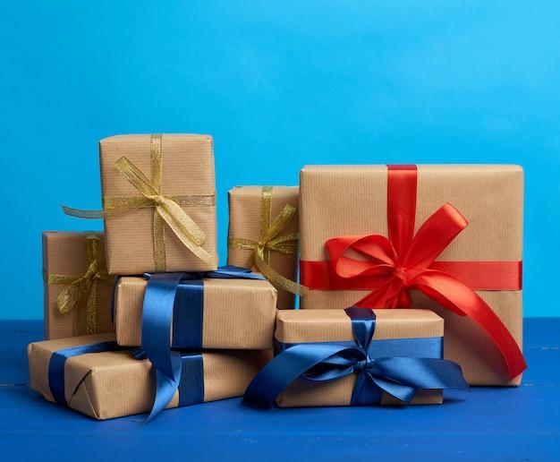 Regalos en cajas envueltas en papel kraft marrón y atadas con cintas de seda sobre un fondo azul.