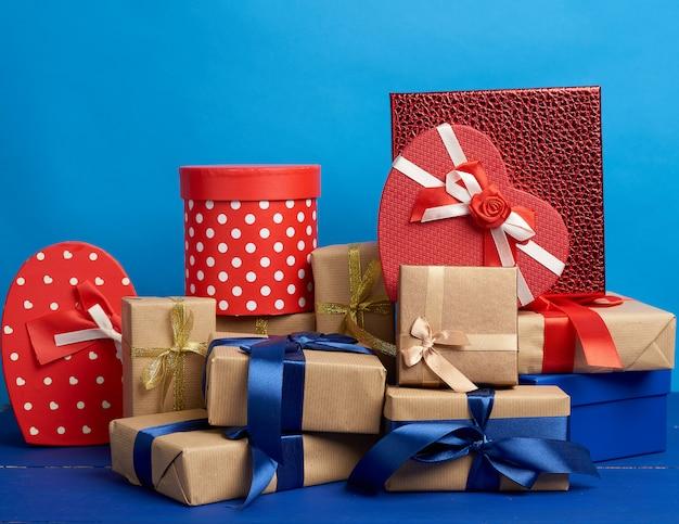 Regalos en cajas envueltas en papel kraft marrón y atadas con cintas de seda.