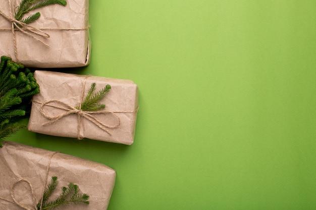 Regalos ecológicos con plantas verdes en papel artesanal sobre una superficie verde