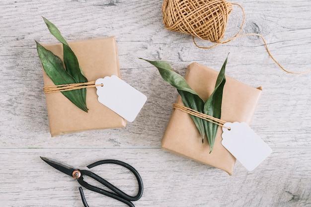 Regalos envueltos con etiqueta y hojas; carrete y tijera sobre fondo con textura de madera