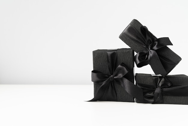 Regalos envueltos en negro sobre fondo liso