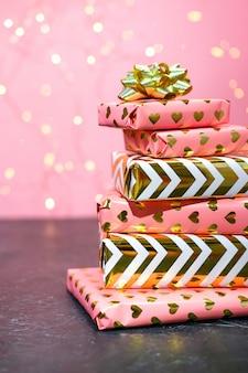 Regalos envueltos en rosa y oro con luces bokeh