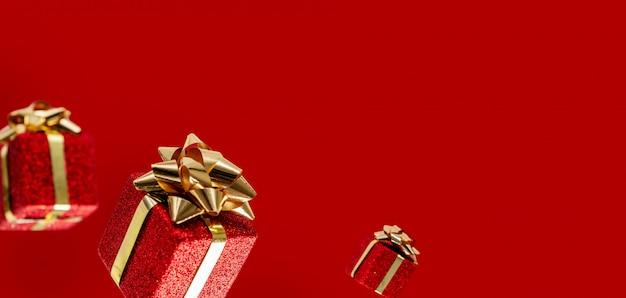 Los regalos están volando en el aire sobre un fondo rojo. rebaja. concepto de levitación. diseño de navidad con espacio de copia.