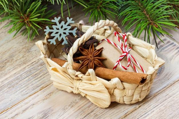 Regalos festivos con cajas, anice estrellado, canasta, canela y copo de nieve