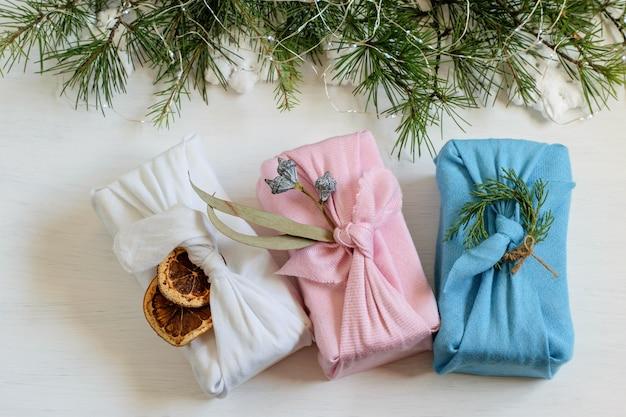 Regalos festivos envueltos en diferentes prendas textiles en estilo furoshiki en el fondo navideño.