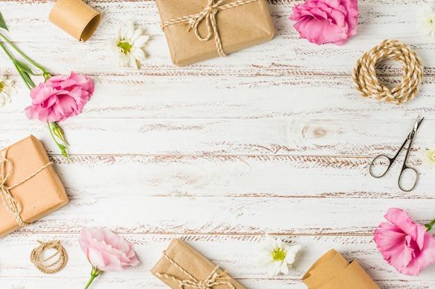 Regalos; flores y tijera dispuestas en patrón circular sobre mesa.