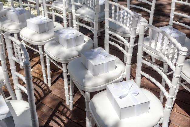 Regalos para invitados a la boda. en sillas blancas.