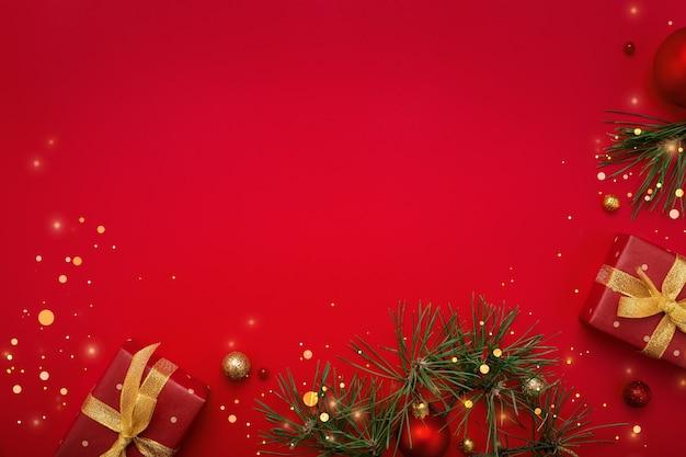 Regalos de navidad y abeto con adornos de oro sobre fondo rojo del espacio de la copia.