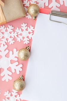 Regalos de navidad, adornos navideños y un cuaderno en blanco abierto en rosa. endecha plana. vista superior.