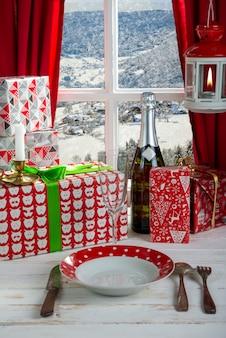 Regalos de navidad, champaña y plato junto a la ventana rústica