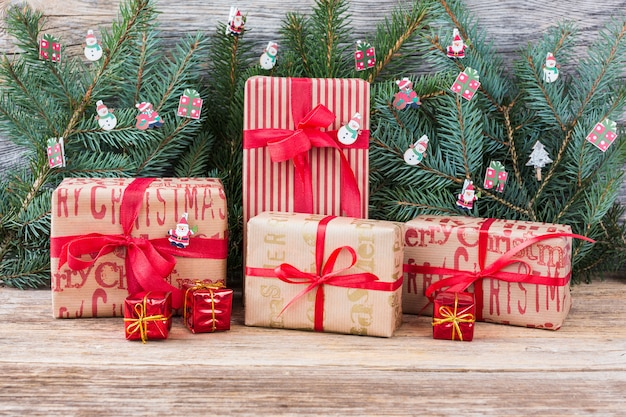 Regalos de navidad con cinta roja y rama de árbol de navidad sobre fondo de madera. estilo vintage, espacio de copia