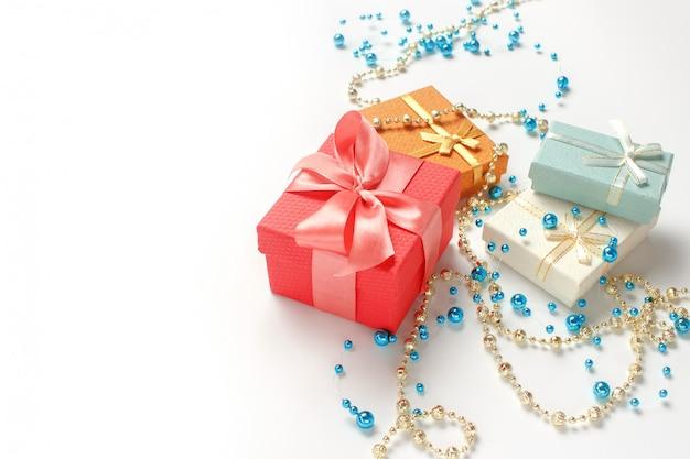 Regalos de navidad, decoraciones de perlas brillantes, brillantes sobre fondo blanco. copia espacio