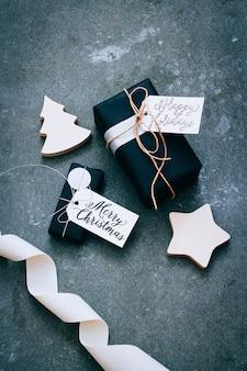 Regalos de navidad en embalaje negro con etiquetas, confeti y decoración de madera sobre un fondo gris