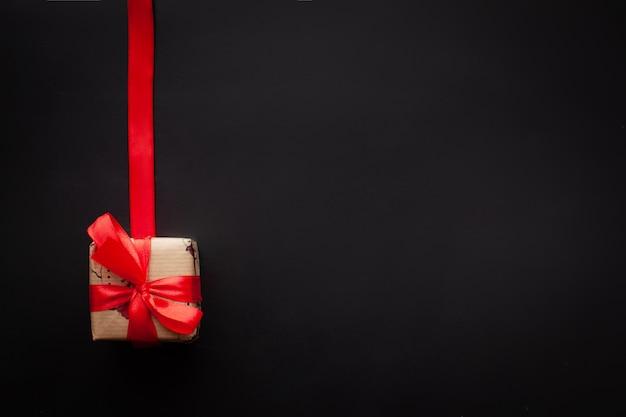 Regalos de navidad envueltos en una cinta roja sobre fondo negro