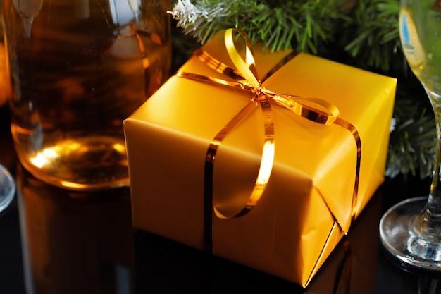 Regalos de navidad envueltos en oro con arcos en la mesa de cerca