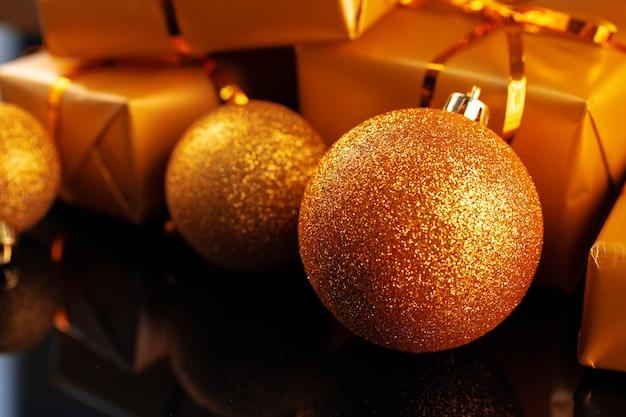 Regalos de navidad envueltos en oro con arcos en la mesa