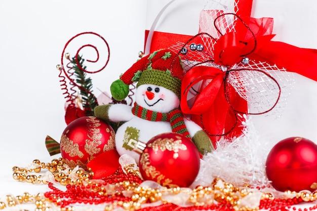Regalos de navidad, muñeco de nieve feliz navidad y adornos navideños sobre un fondo blanco.