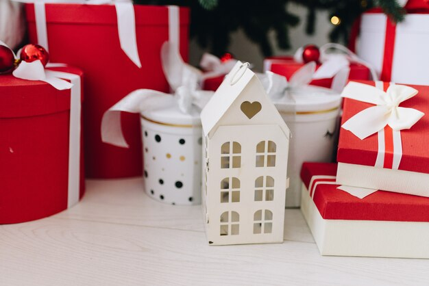 Regalos de navidad y objetos en rojo y blanco debajo del árbol de navidad.
