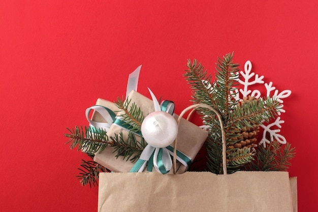 Regalos de navidad en papel kraft con cintas verdes y blancas y rama de abeto en bolsa de papel. regalos navideños. endecha plana. día de san esteban. vista superior