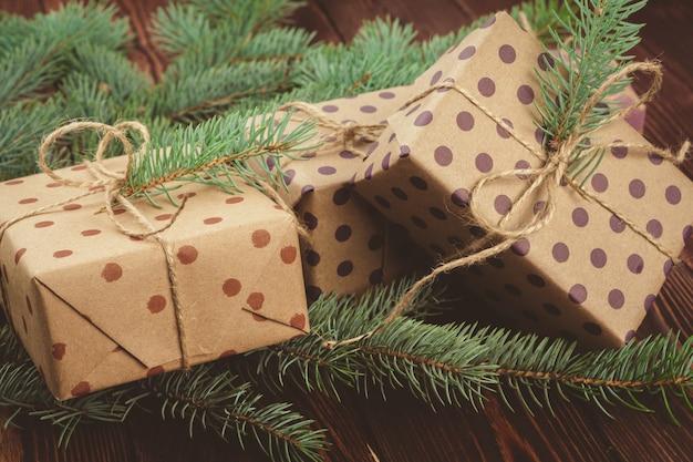 Regalos de navidad y ramas de pino en mesa de madera, vista superior